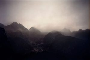 A misty mountain range photograph in purple tones.