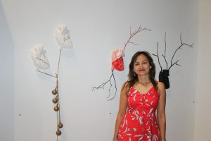 Anatomical heart shaped sculptured mounted on wall. Female artist stands next to it in a red dress.