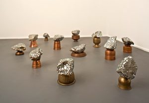 A grouping of rock like shapes with silver metal embedded in them. Each  shape is balanced on a copper pot, vase or bowl.