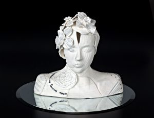 A white ceramic bust of a person sitting on a round mirror with a black background. There are textural patterns on the skin and flowers and leaves in the hair.
