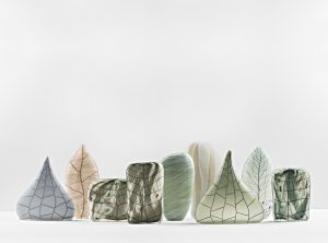 A group of 9 glass sculptures. Each is a different colour and shape but all have detailed linear patterning on them.